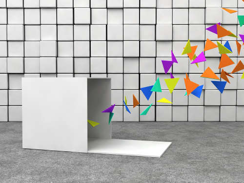 opened cube and colorful triangles in front of cubes wall and cement floor.